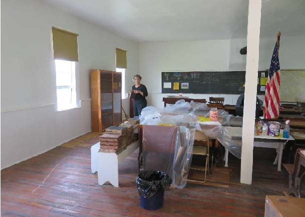 Photo of historic schoolhouse with freshly painted walls and plastic-covered furnishings